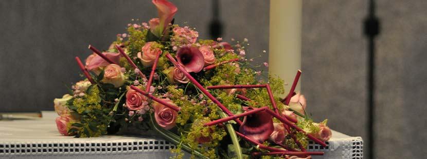 Blumenschmuck auf einem Sarg bei der Trauerfeier.