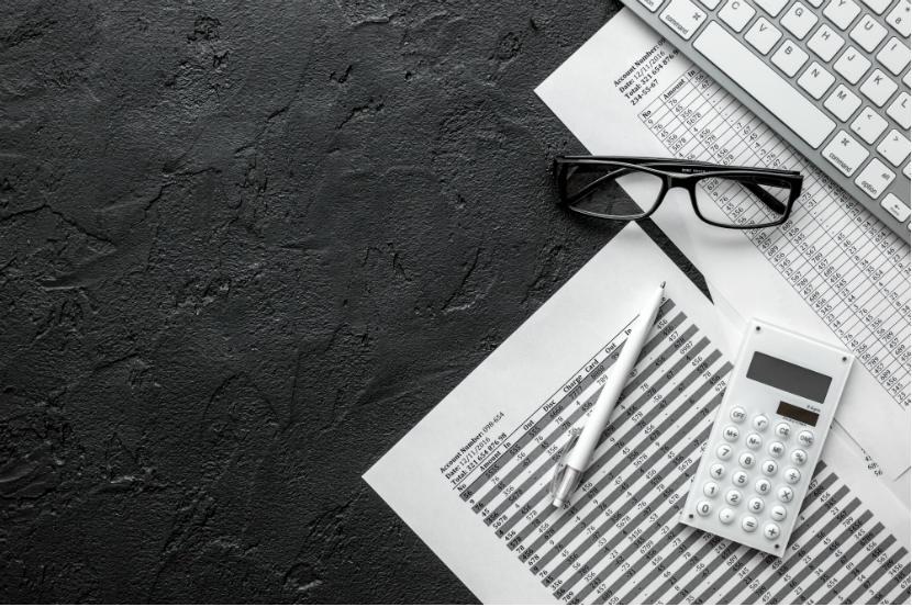 Steuerberater Graz: Büromaterial (weiß) vor schwarzem Hintergrund.