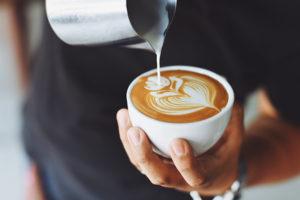 Kaffeehaus Linz: Eine Person bereitet einen Milchkaffee zu