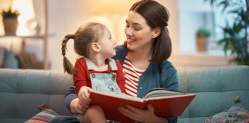 Junge hübsche Mutter, die ihrer kleinen Tochter ein Buch vorliest. Kinderbücher Wien.