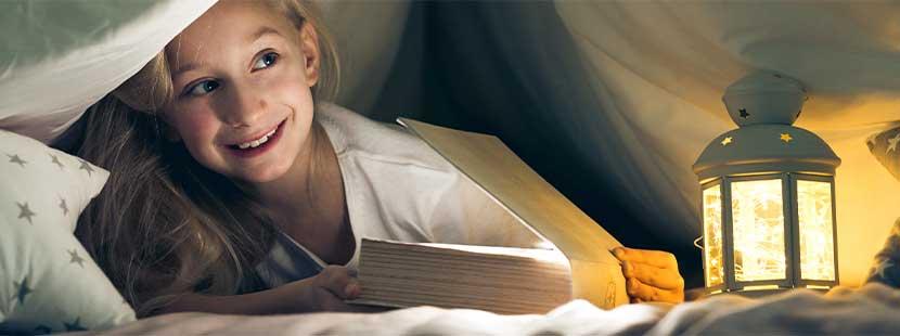 Blondes Mädchen, das nachts unter der Decke ein Buch liest. Kinderbuchhandlung Wien.