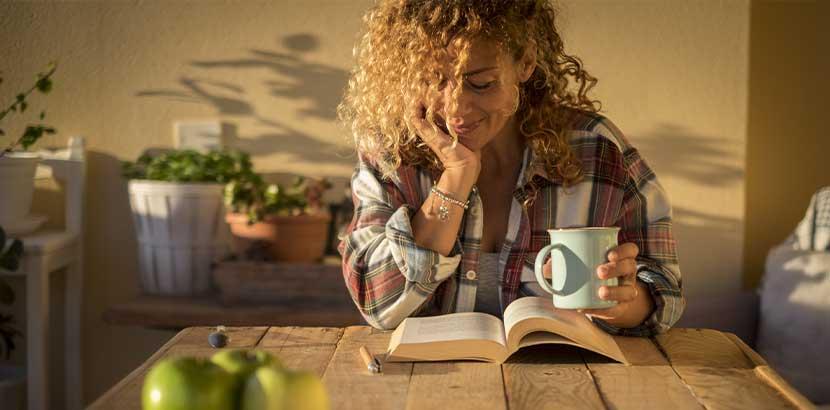 Junge Frau, die in ihrer Küche sitzt und ein Buch liest. Kinderbuchhandlung Wien.