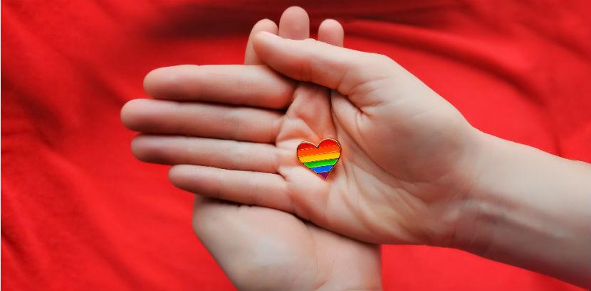 Geschlechtskrankheiten: gefaltene Hände bin buntem Herz vor rotem Hintergrund
