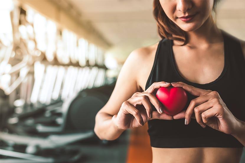 Junge dunkelhaarige Frau im Fitnessstudio, die ein kleines rotes Herz vor ihren Oberkörper hält. Sportmediziner Wien.