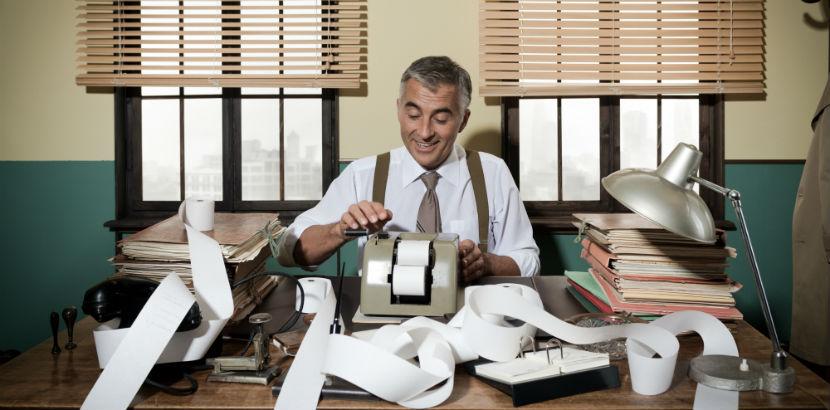 Steuerberater Wien: Ein Vintage_Buchhalter sitzt vor seinem Schreibtisch.