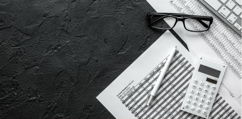 Steuerberatung Wien: Weißes Büromaterial auf schwarzem Tisch.