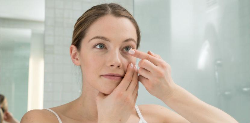 Optiker Wien: Eine Frau setzt sich Kontaktlinsen ein.