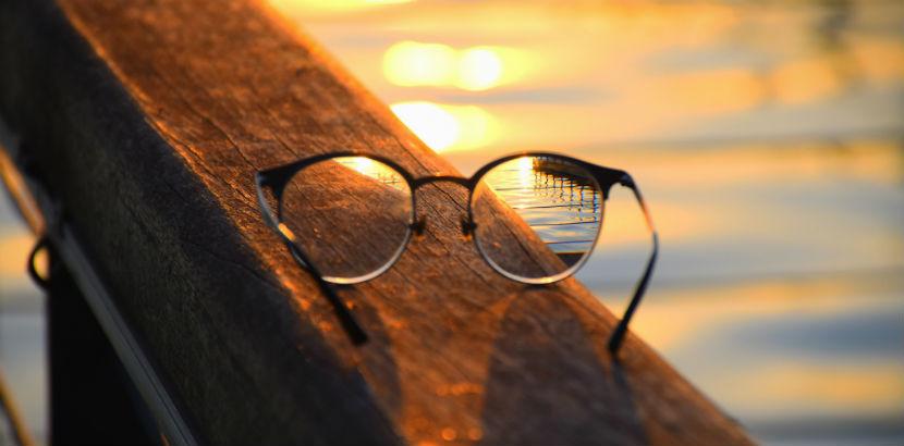 Optiker Wien: Eine Brille auf einer Holzbalustrade eines Piers.