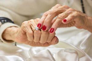 Alte Frau mit schön manikürten Fingern, die einen Diamantring an ihrem Finger berührt. Diamantbestattung Österreich.