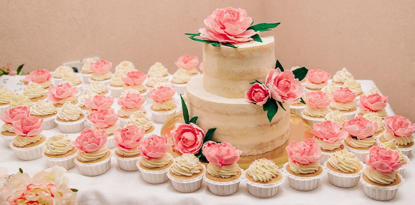Kleine Hochzeitstorte und passende Cupcakes im Vintage-Stil.