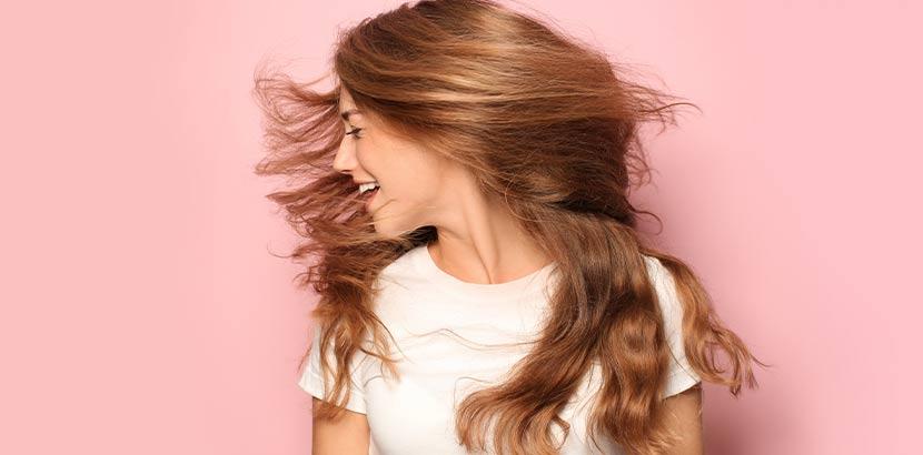 Junge Frau mit starkem, schönem Haar nach der PRP Haare Behandlung vor rosafarbenem Hintergrund.