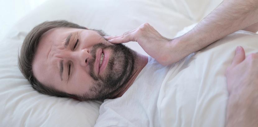 Ein Mann mit Karies an einem Zahn im Unterkiefer, der im Bett liegt.