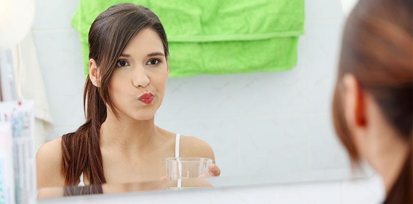 Eine Frau beim Gurgeln mit Salz Wasser gegen Karies Befall auf ihrem Zahn.