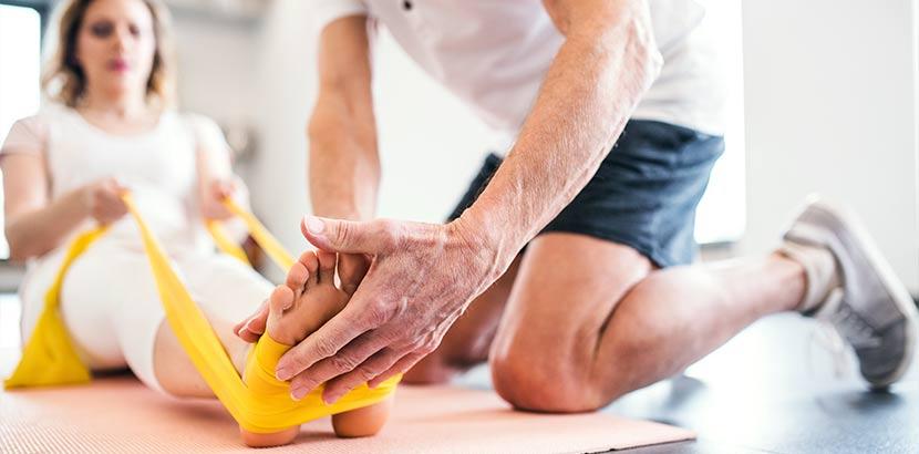 Physiotherapeut, der mit einer Patientin arbeitet. Welcher Arzt wofür?