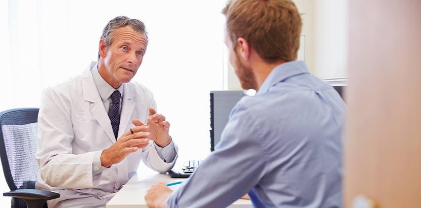 Junger Mann beim Arzt in der Beratung. Welcher Arzt wofür zuständig?