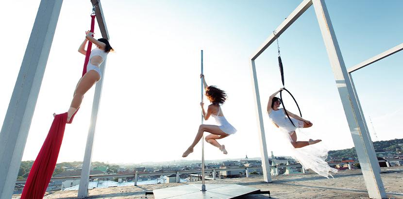 Aerial Silk Wien, Aerial Hoop Wien, Aerial Poledance Wien: Drei Frauen üben an Tüchern, Stange und Reifen Aerial Fitness Übungen aus