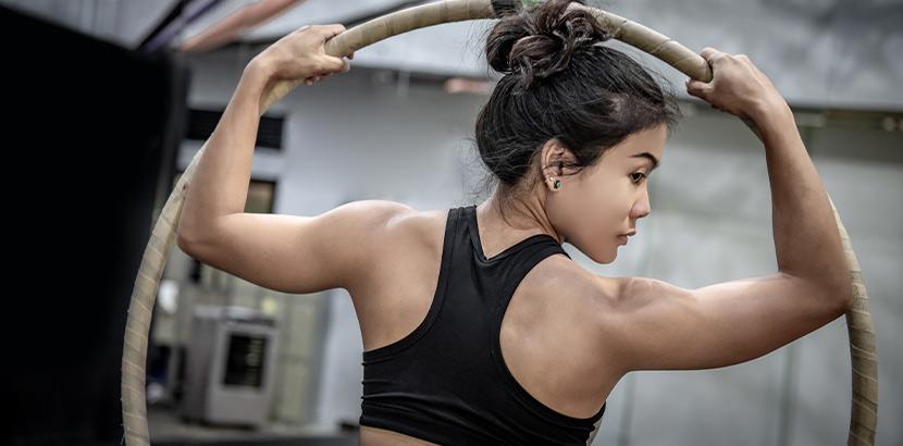 Aerial Hoop: eine Frau mit trainierten Muskeln mit einem Aerial Reifen