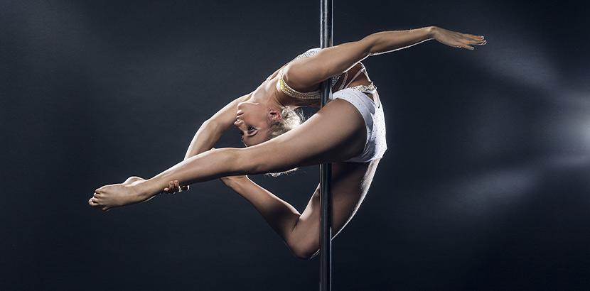 Poledance Wien: eine Frau tanz kunstvoll an einer Poledance Stange