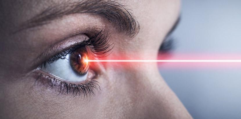 Ein Laserstrahl der auf die Hornhaut eines Auges trifft. Augenarzt Graz.