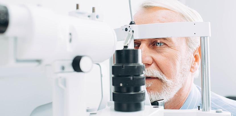 Ein Mann mit grauem Haar blickt in eine Spaltlampe zur Augenuntersuchung. Augenarzt Graz.