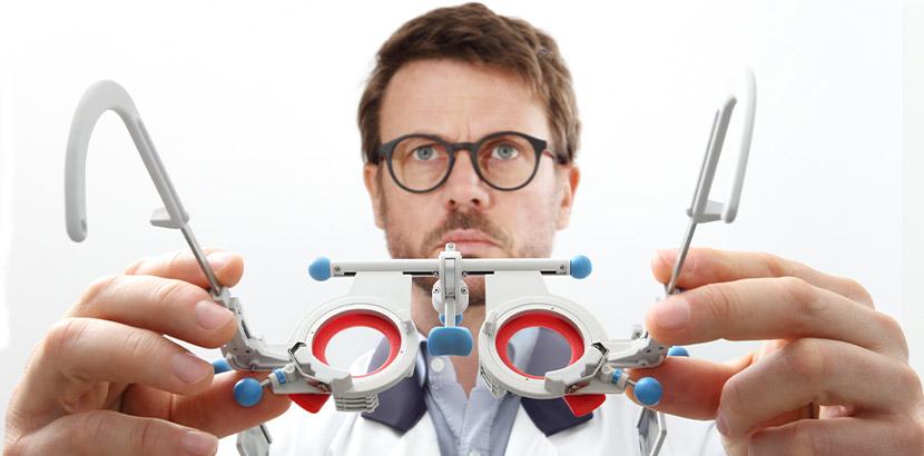 Ein Augenarzt hält eine Testbrille in Richtung der Kamera, um sie dem Patienten aufzusetzen. Augenarzt Graz.