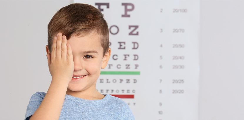 Ein Junge, der vor einem Sehtest steht und sich ein Auge mit der Hand zuhält. Augenarzt Linz.