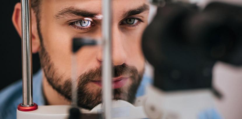 Ein Mann mit Bart, der für einige Zeit in die Spaltlampe eines Augenarztes schaut. Augenarzt Linz.