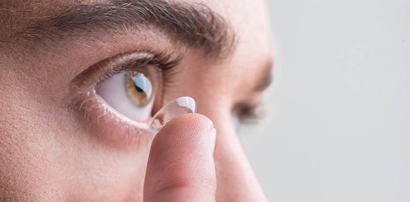 Eine Nahaufnahme eines Fingers, der eine Kontaktlinse auf ein Auge auflegt. Augenarzt Linz.