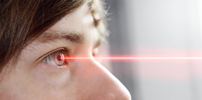 Eine Nahaufnahme von dem Auge einer Frau, auf das ein roter Laserstrahl trifft. Augenarzt Linz.