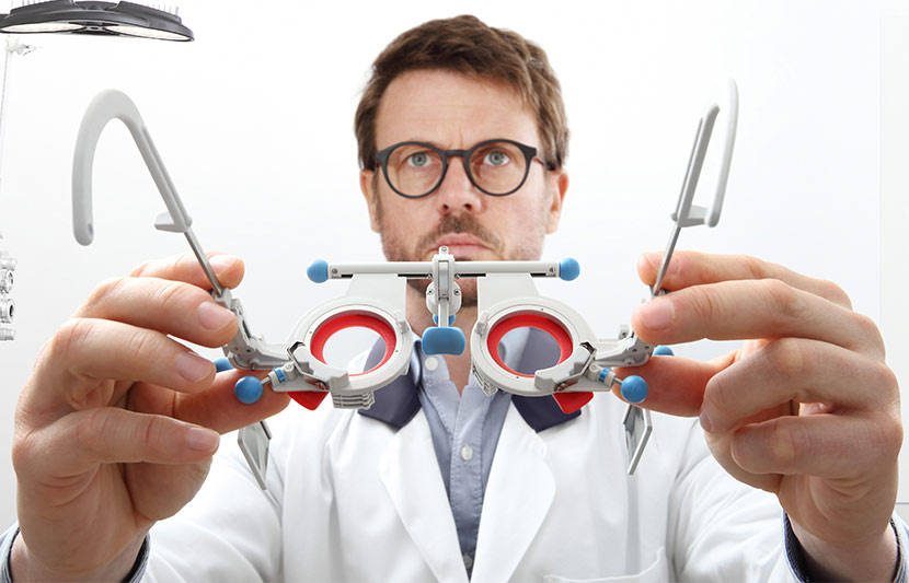 Ein Augenarzt, der eine Testbrille in Richtung der Kamera hält als würde er sie einem Patienten aufsetzen. Augenarzt Linz.