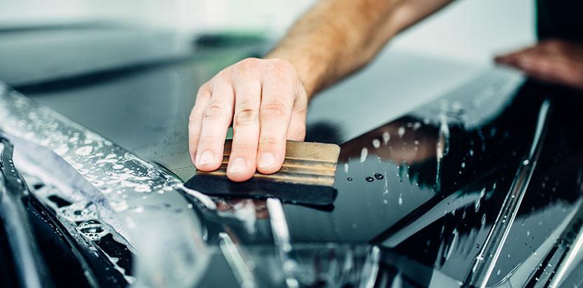 Eine transparente Fahrzeugfolierung wird mit einem Werkzeug von Blasen befreit. Auto folieren.
