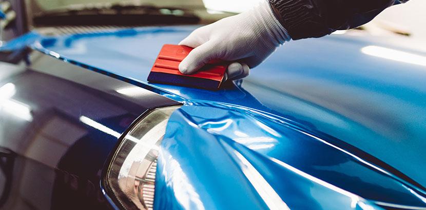 Eine blaue Autofolie auf einer Motorhaube wird mit einem Werkzeug geglättet. Auto folieren.