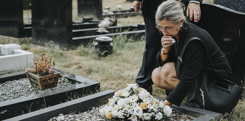 Ältere Frau mit grauen Haaren und Trauerkleidung, die an einem frischen Grab trauert. Bestatter Wien.