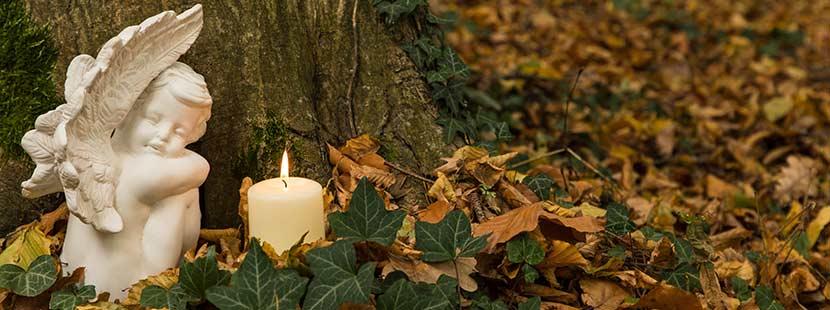 Kleiner weißer Engel neben einer brennenden weißen Kerze an einem herbstlichen Grab. Bestatter Wien.