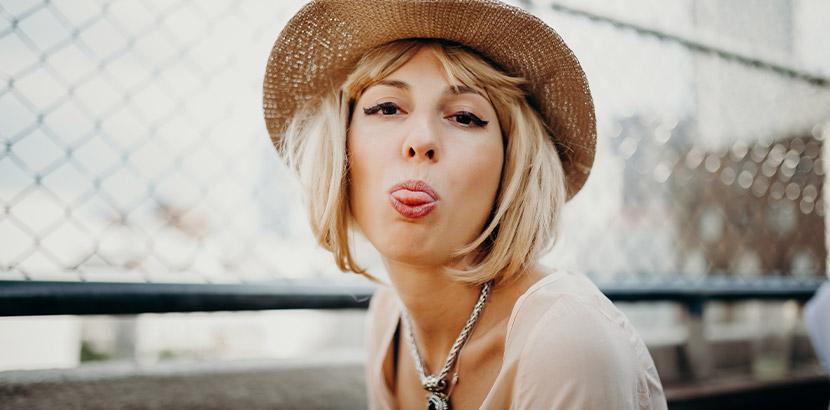 Junge blonde Frau mit einer Echthaarperücke, die frech in die Kamera lächelt.