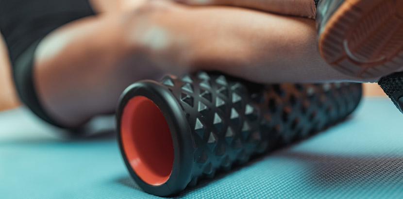 Eine Frau trainiert mit einer Massagerolle ihre Waden