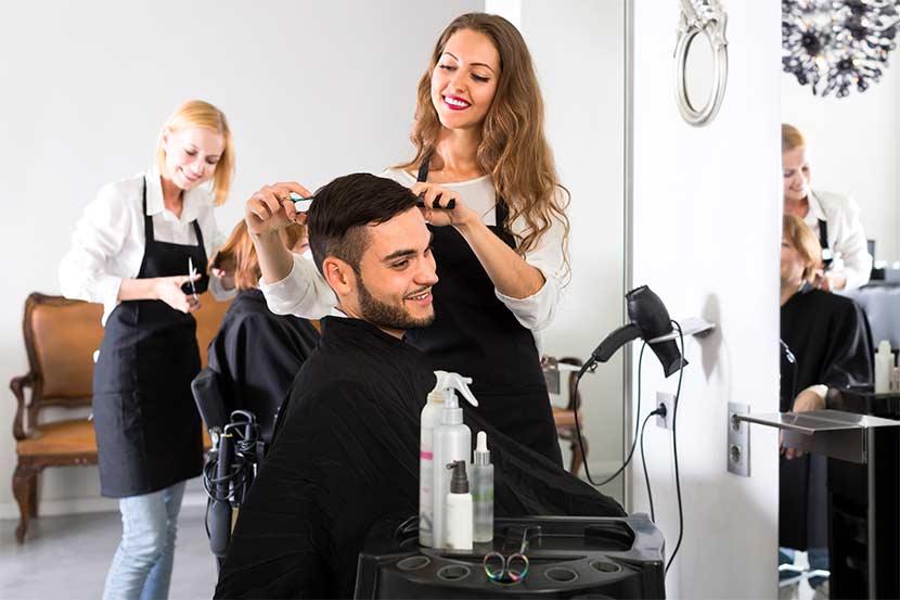 Junge brünette Friseurin, die einem dunkelhaarigen Mann die Haare schneidet. Friseur Linz.