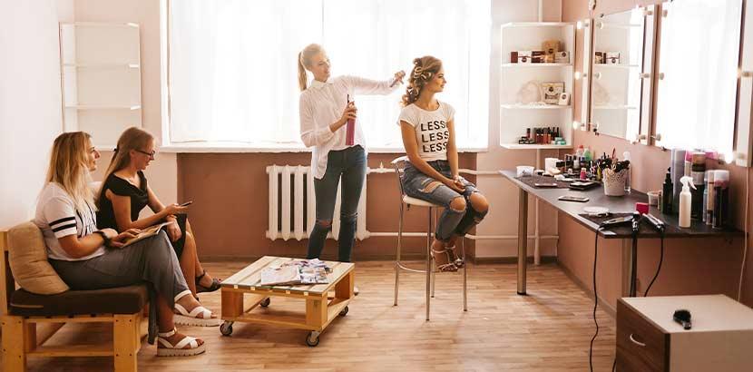 Innenansicht eines Friseursalons mit zwei Kundinnen, die warten, und einer Kundin, die gerade von der Friseurin mit einer Haarverlängerung bedient wird.