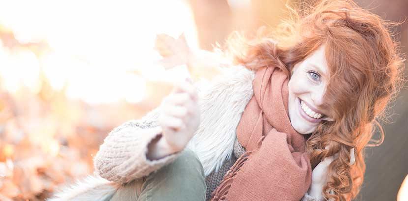 Hübsche junge Frau mit roten Henna-Haaren vor herbstlichem Hintergrund. Friseur Linz.