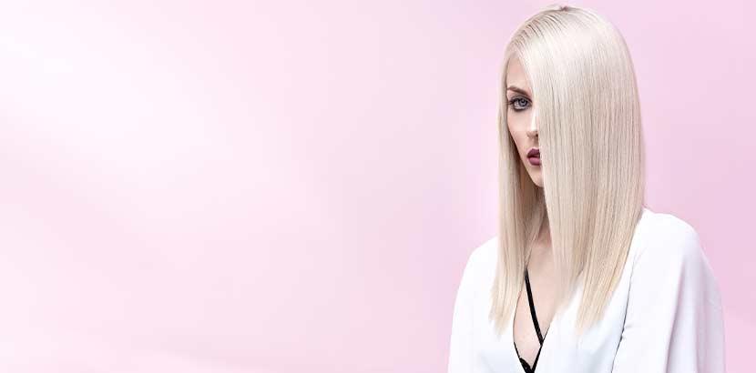 Junge Frau mit weißblond gefärbten langen Haaren vor rosa Hintergrund. Friseur Linz.