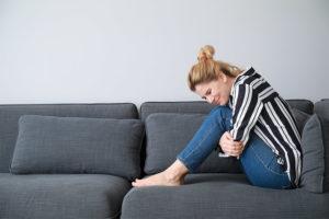 Junge blonde Frau, die sich vor Magenschmerzen auf einem Sofa windet. Gastroenterologe Wien.
