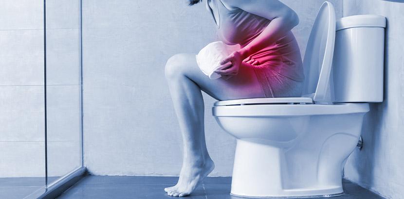 Junge Frau, die auf der Toilette sitzt und Schmerzen beim Stuhlgang hat.