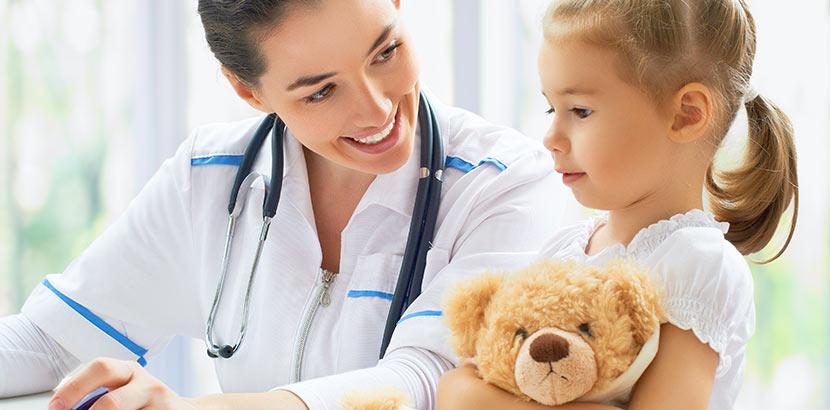 Eine Kinderärztin spricht mit einem jungen Mädchen, das einen Teddybären festhält.