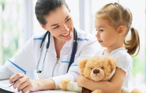 Eine Kinderärztin spricht mit einem jungen Mädchen, das einen Teddybären festhält. Kinderarzt Wien.