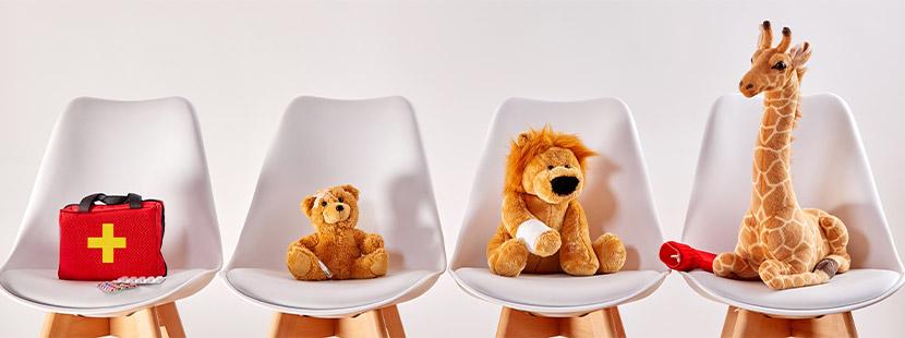 Stofftiere, die im Wartezimmer auf Stühlen sitzen.