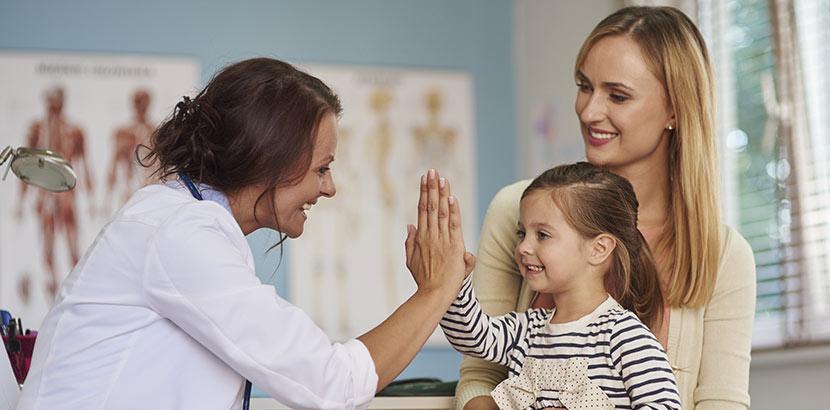 Ein junges Mädchen sitzt auf dem Schoß ihrer Mutter und gibt der Kinderärztin ein High Five. Kinderarzt Wien.