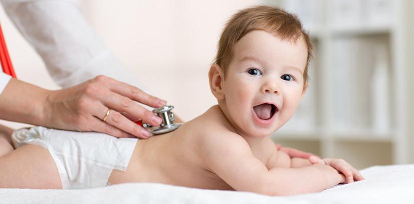 Eine Kinderärztin verwendet ein Stethoskop um die Daten des Herzschlags eines fröhlichen Babys zu messen.