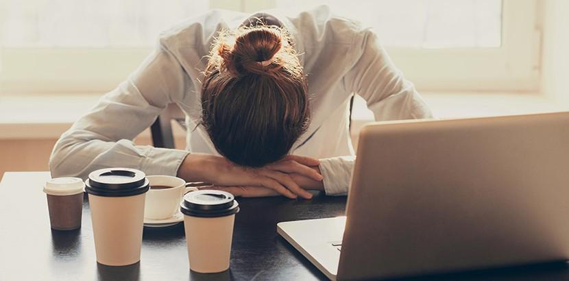 Frau mit Magnesiummangel ist müde und trinkt deswegen viel Kaffee