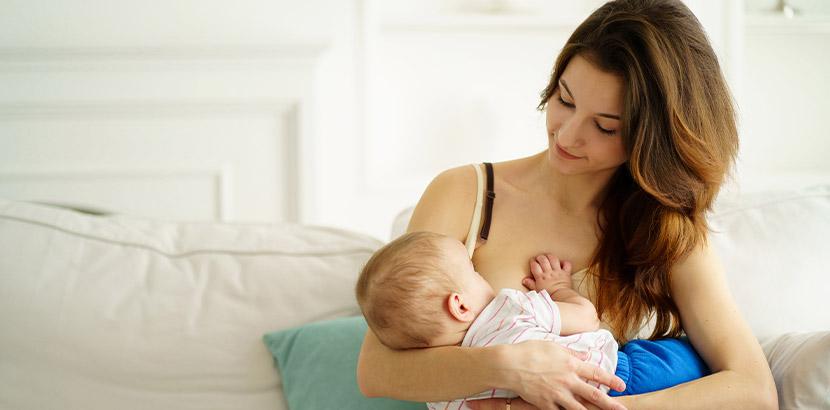 Junge Mutter, die ihren Säugling stillt. Säuglinge mit Neurodermitis.
