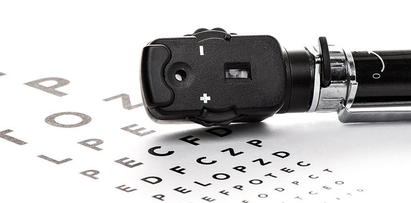 Ein Ophthalmoskop (Augenspiegel) das auf einem Sehtest liegt. Augenarzt Graz.